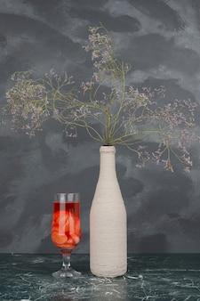 Bouteille avec fleurs fanées et verre de jus sur mur de marbre.