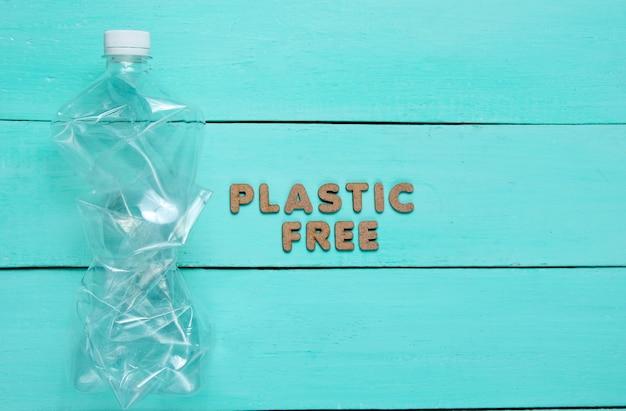 Bouteille froissée sur une surface en bois bleue avec texte sans plastique