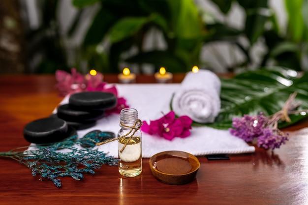 Une bouteille avec de l'huile aromatique, une tasse avec de l'huile versée située devant une serviette éponge sur laquelle sont posées des pierres pour la thérapie, des fleurs roses et des brins de lavande séchés