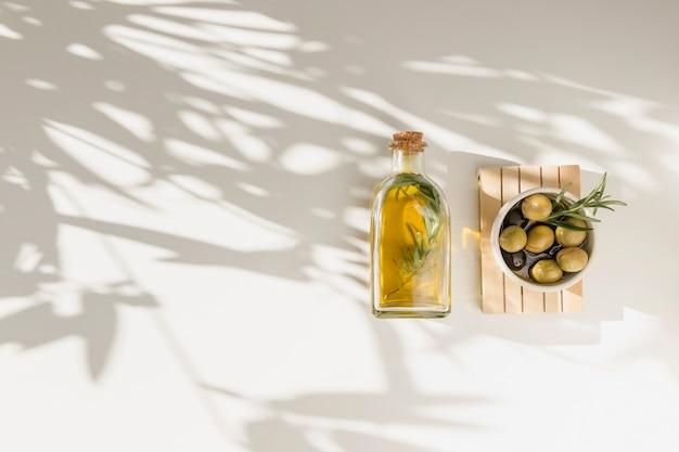 Bouteille d'huile et bol d'olives sur planche de bois sur fond blanc