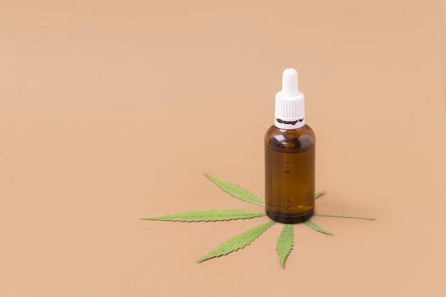 Bouteille d'huile de cannabis avec feuille verte sur fond beige avec espace pour texte concept de cannabis médical
