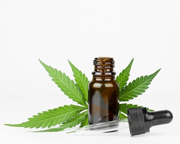 Bouteille avec de l'huile de chanvre et des feuilles de cannabis sur fond clair