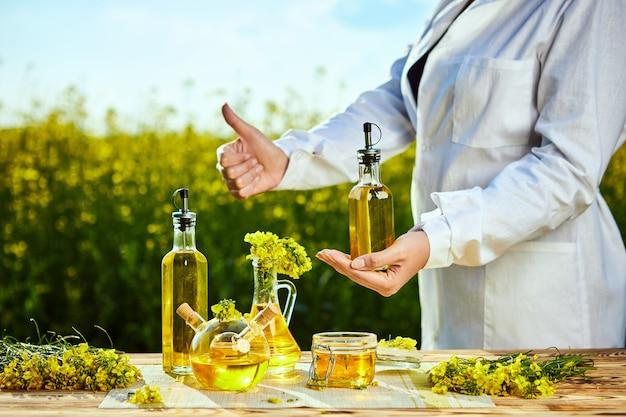 Bouteille d'huile de colza à la main d'un agronome ou biologiste sur fond de champ de colza