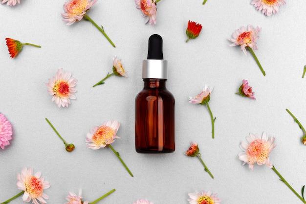 Bouteille d'huile cosmétique sur les boutons floraux à plat