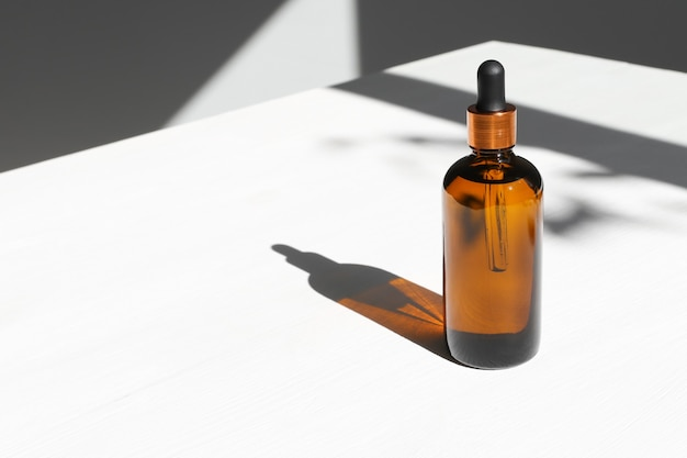 Bouteille d'huile cosmétique brune en verre sur une table en bois et avec reflet et reflet du soleil
