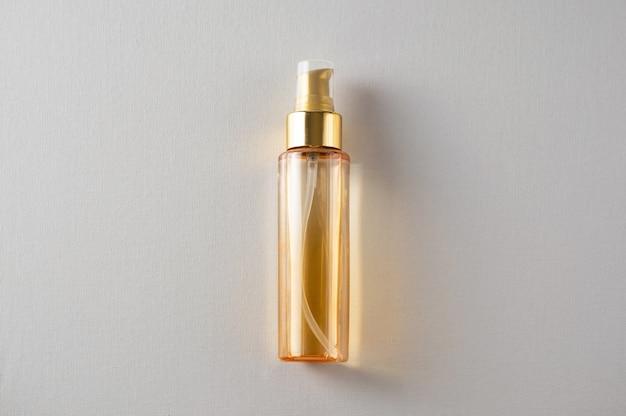 La bouteille d'huile cosmétique jaune