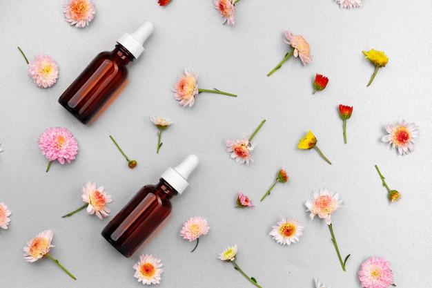 Bouteille d'huile cosmétique sur le mur de bourgeons floraux à plat
