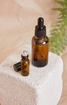 Bouteille d'huile cosmétique en verre brun avec pipette et récipient cosmétique de baume à lèvres