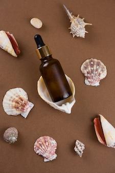 Bouteille d'huile cosmétique vue de dessus sur fond marron avec motif de coquilles