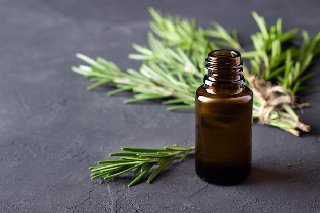 Une bouteille d'huile essentielle avec des brindilles de romarin frais sur une table en pierre sombre.