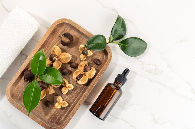 Bouteille d'huile essentielle de camélia et graines de camélia sur plateau en bois. beauté, soins de la peau, bien-être