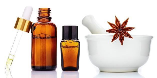 Bouteille d'huile essentielle de cannelle avec des bâtons de cannelle de ceylan et étoile d'anis isolé sur blanc.