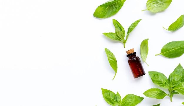 Une bouteille d'huile essentielle avec des feuilles de basilic frais