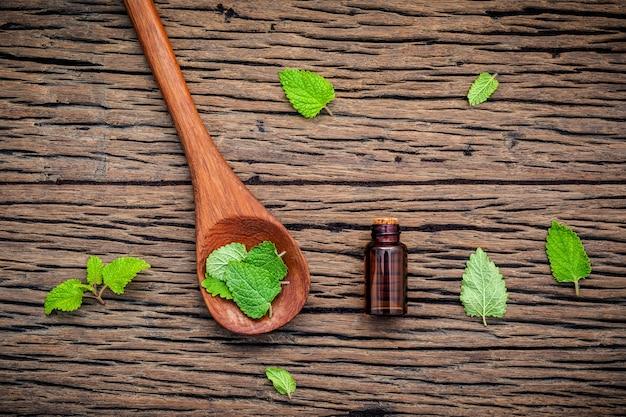 Bouteille d'huile essentielle avec des feuilles de mélisse fraîche sur une table en bois.