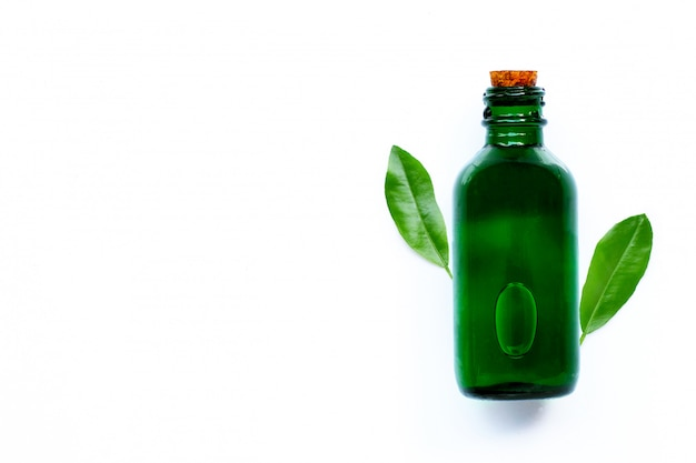 Bouteille d'huile essentielle avec des feuilles vertes