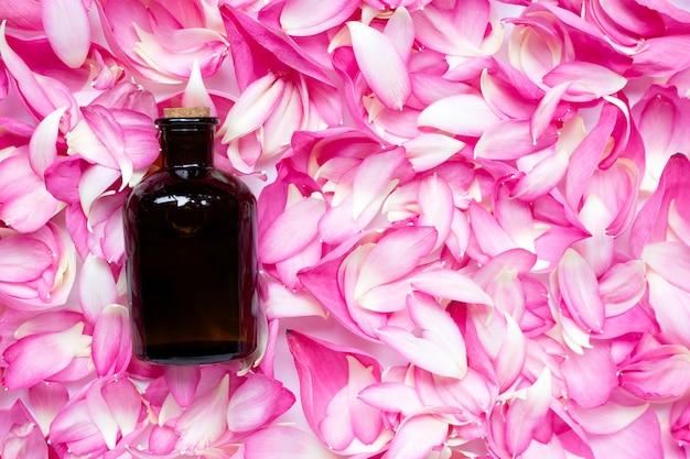 Bouteille d'huile essentielle sur fond de pétales de lotus rose.