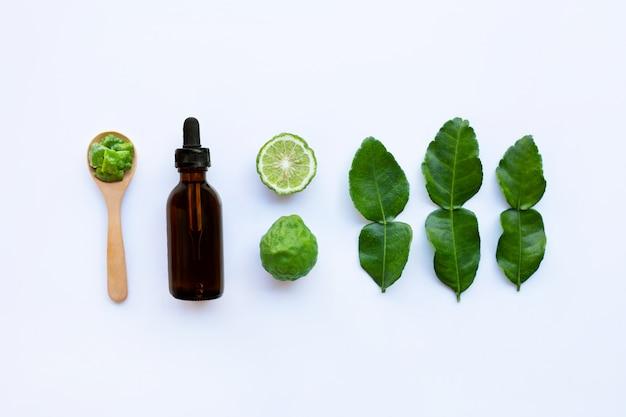 Bouteille d'huile essentielle et de fruits de bergamote fesh avec des feuilles sur blanc