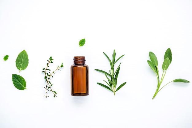 Bouteille d'huile essentielle avec des herbes fraîches sur une table en bois blanche.