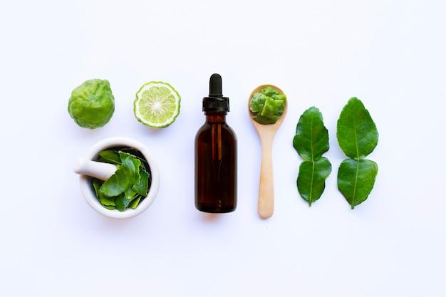 Bouteille d'huile essentielle et de limes de kaffir fraîches ou de fruits de bergamote avec des feuilles