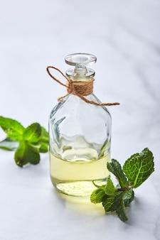Bouteille avec de l'huile essentielle de menthe et des ingrédients biologiques naturels de feuille verte pour les cosmétiques soins de la peau traitement du corps concept de soins de beauté