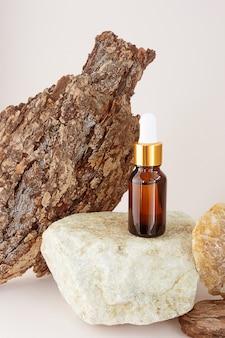 Une bouteille d'huile essentielle naturelle sur une pierre, à côté d'une écorce d'arbre avec une belle texture. concept d'essences naturelles, cosmétiques bio, aromathérapie, spa.