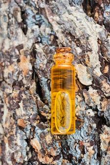 Une bouteille d'huile essentielle naturelle repose sur l'écorce d'un arbre avec une belle texture. concept d'essences naturelles, cosmétiques bio, aromathérapie, spa. mise à plat.
