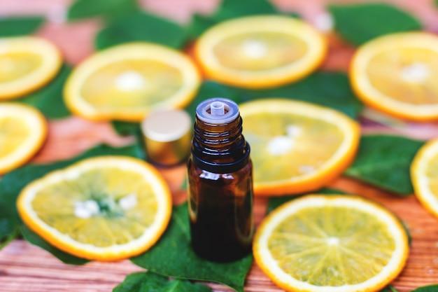 Bouteille d'huile essentielle d'oranges sur bois