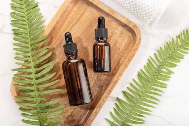 Bouteille d'huile essentielle sur plateau en bois. beauté, soins de la peau, bien-être