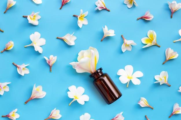 Bouteille d'huile essentielle avec plumeria ou fleur de frangipanier sur une surface bleue