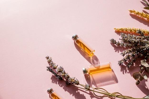 Bouteille d'huile essentielle avec sauge à base de plantes fraîches, lavande.appartement posé sur un mur rose.huile saine.le concept d'une alimentation végétarienne saine, détox.médecine alternative, phytothérapie, traitement à base de plantes.