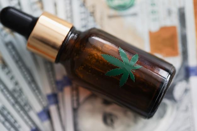 Une bouteille d'huile de marijuana se trouve sur les billets de banque