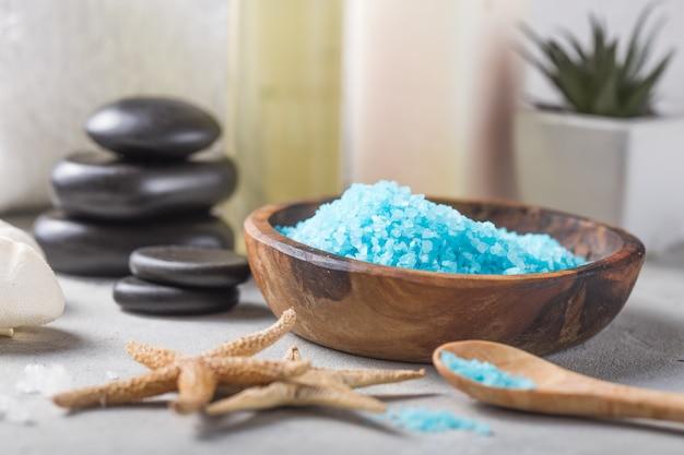 Bouteille d'huile de massage arôme sel de parfum essentiel et naturel avec des pierres, des bougies sur une table en béton gris.