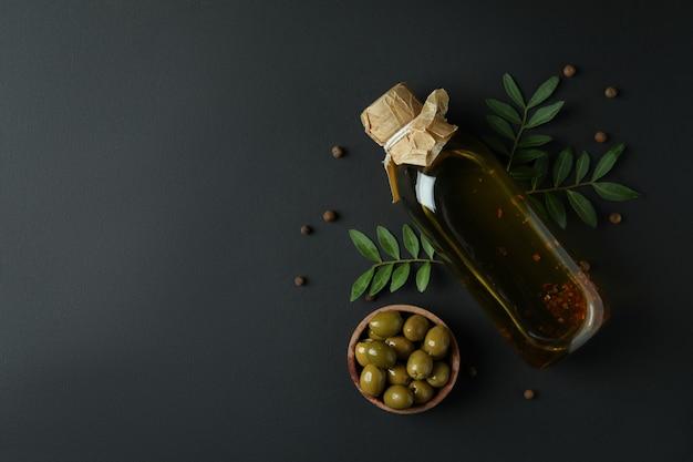 Bouteille d'huile d'olive, bol d'olives, brindilles et poivre sur fond noir