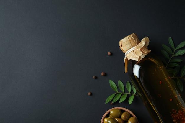 Bouteille d'huile d'olive, bol d'olives, brindilles et poivre noir
