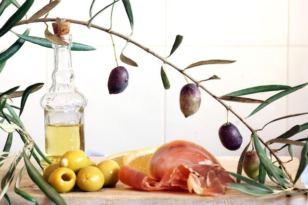 Une bouteille d'huile d'olive, une branche d'olivier et un petit-déjeuner léger composé d'olives farcies et d'un jambon.