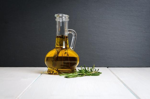 Bouteille d'huile d'olive, branche de romarin frais sur table en bois blanc