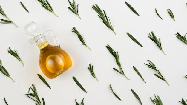 Bouteille d'huile d'olive avec des feuilles à côté de la table