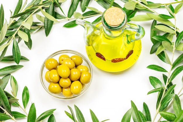 Une bouteille d'huile d'olive et d'olives dans un bol en verre sur fond blanc.