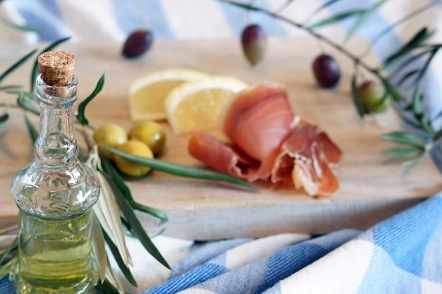 Bouteille d'huile d'olive sur un petit-déjeuner avec olives et bacon le matin.
