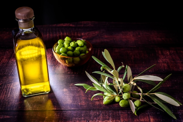 Bouteille d'huile d'olive vierge à côté d'un bouquet d'olives crues sur fond sombre.