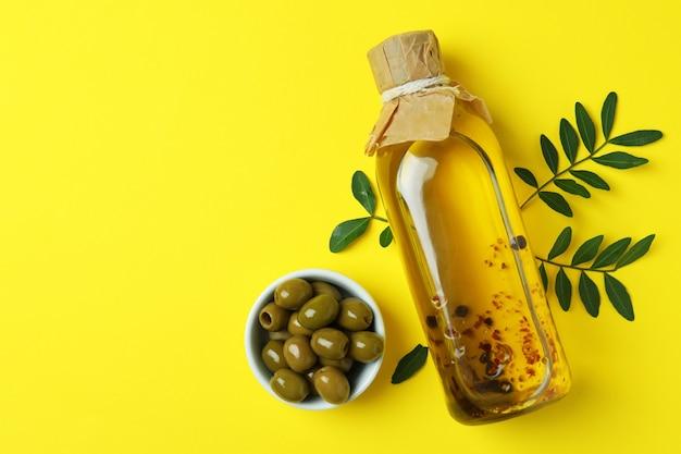 Bouteille d'huile, olives et brindilles sur jaune