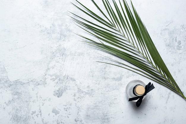 Bouteille d'huile de parfum et feuille verte de palmier sur fond de béton. vue de dessus, mise à plat