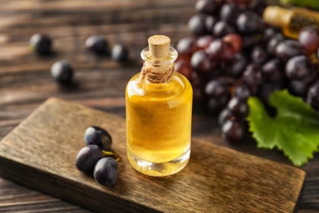 Bouteille d'huile de pépins de raisin sur planche de bois