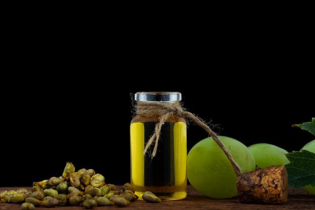 Bouteille avec de l'huile de raisin, des grains de raisin et une grappe de raisin blanc en arrière-plan.