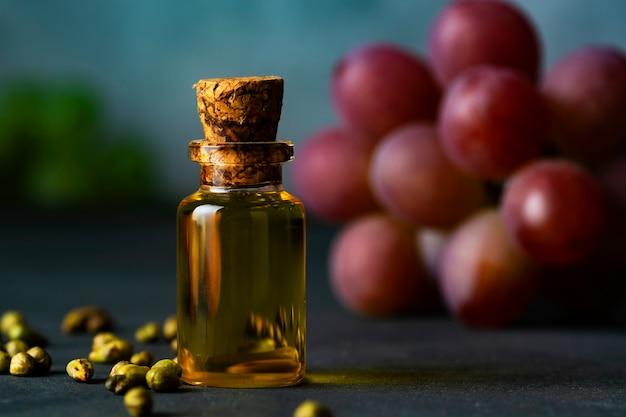 Bouteille avec de l'huile de raisin, des grains de raisin et une grappe de raisin rose en arrière-plan.