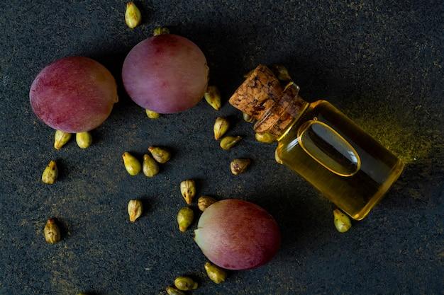 Bouteille d'huile de raisin, de grains de raisin et de raisins roses.