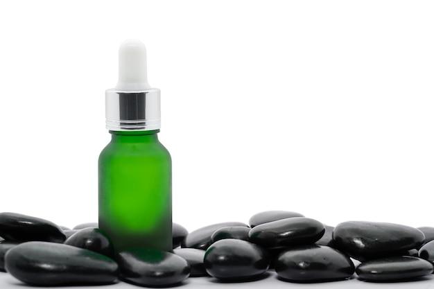 Bouteille d'huile de sérum compte-gouttes maquette ou huile essentielle avec pierre noire sur fond blanc