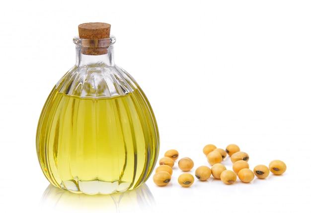 Bouteille d'huile et soja sur espace blanc