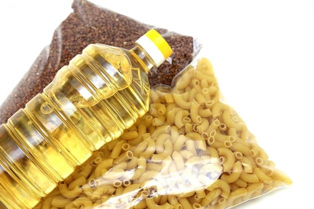 Une bouteille d'huile végétale, de sarrasin et de pâtes sont isolés sur un mur blanc. le concept de don.