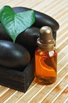 Bouteille d'huiles cosmétiques avec des pierres de spa